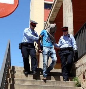 Un dels detinguts conduït pels Mossos durant l'escorcoll